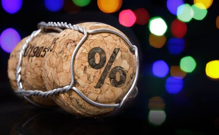 Champagne cork with the shape of a percent symbol burnt in and colorful blurry lights in the background.(series)