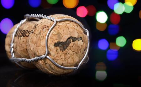 Champagne cork with the shape of American Samoa burnt in and colorful blurry lights in the background.(series)