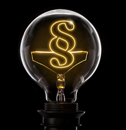 unlawful act: Clean and shiny lightbulb with a paragraph symbol as a glowing wire.(series) Stock Photo