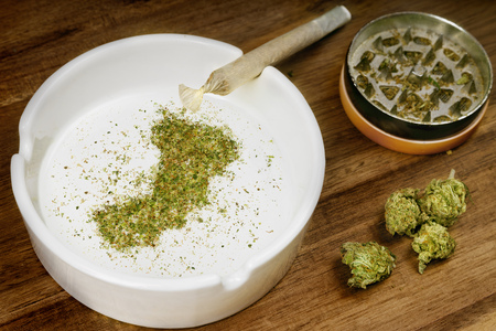 Crumbled weed in the shape of Oman and a joint. Stock Photo