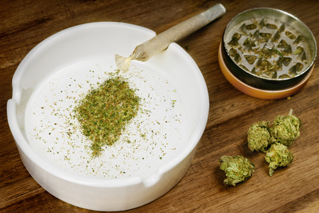 Crumbled weed in the shape of Sao Tome and Principe and a joint.