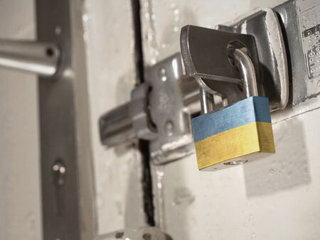 A bolted door secured by a padlock with the national flag of Ukraine on it.(series) Banco de Imagens
