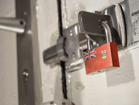 A bolted door secured by a padlock with the national flag of Manitoba on it.(series) Banco de Imagens