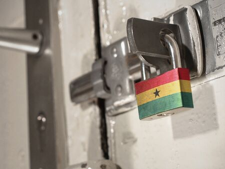 A bolted door secured by a padlock with the national flag of Ghana on it.(series) Banco de Imagens