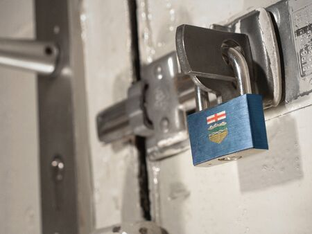 A bolted door secured by a padlock with the national flag of Alberta on it.(series) Banco de Imagens
