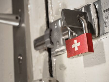 A bolted door secured by a padlock with the national flag of Switzerland on it.(series)