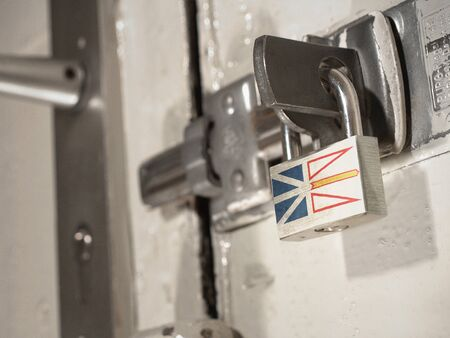 A bolted door secured by a padlock with the national flag of Newfoundland on it.(series)