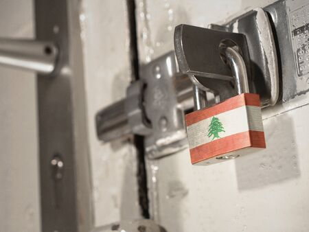 A bolted door secured by a padlock with the national flag of Lebanon on it.(series) Banco de Imagens