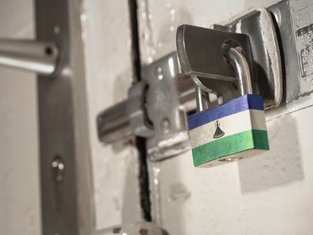 A bolted door secured by a padlock with the national flag of Lesotho on it.(series) Banco de Imagens