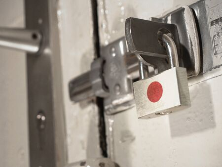 A bolted door secured by a padlock with the national flag of Japan on it.(series)