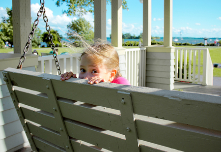 Playful girl hiding on swing bench in the park