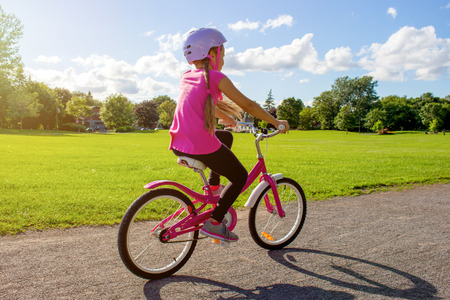 Girl in a helmet riding a bicycle. Cyclist in summer park. Stockfoto - 115663849