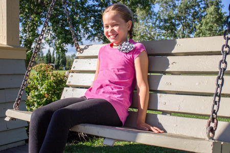 Smiling girl sitting on swing bench in the park Stockfoto - 115664162