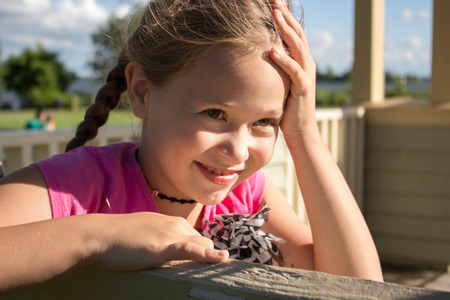 Smiling dreamy beautiful girl sitting on a bench in the park Stockfoto - 115664165