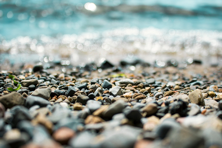 Waves washing over gravel beach, macro shot with narrow focus background