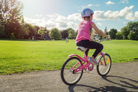 Girl in a helmet riding a bicycle. Cyclist in summer park. Stockfoto - 115664168