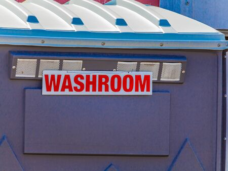 """A portable toilet enclosure stands outside. The roof and top section of it are seen, with a red sign reading """"Washroom"""" affixed to the side."""