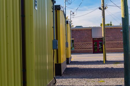 Yellow portable classrooms are standing in gravel outside an elementary school. The temporary buildings house additional students as the school needs to support a growing local population.