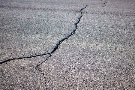 A road paved with asphalt has a large crack across it, which forks into two in the foreground. Imagens