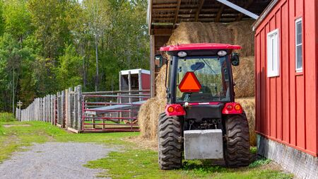 A small, red tractor is parked beside a barn and bales of hay on a farm.