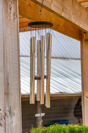 Metallic wind chimes are hanging from a wooden beam, part of an outdoor gazebo in a garden. Viewed up close, the reflective texture of these decorative music-makers can be seen.