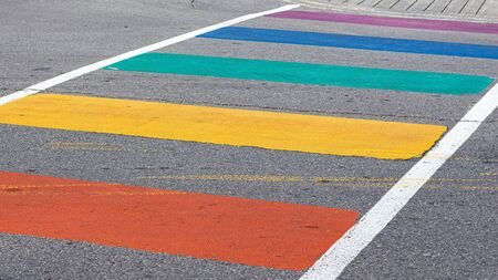 A crosswalk is painted with rainbow-colored stripes during Gay Pride celebrations in a city.