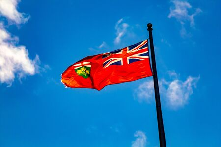 The flag of the Canadian province of Ontario flies in the wind against a blue sky. It blows to the left of its flagpole against a bright blue sky with scattered clouds.