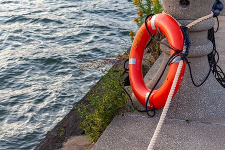 A circular orange lifesaver ring is tied up on a pier by coastal water. The life-preserving safety device stands ready to help save drowning swimmers or boaters.