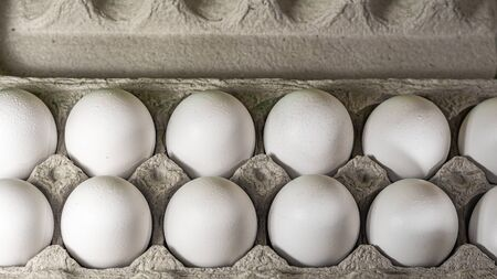 A typical egg carton containing one dozen white chicken eggs is viewed up close from above, filling the frame. Stock fotó