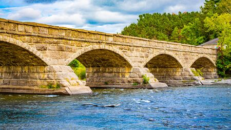 An old stone bridge provides crossing over a river as water rushes through its arches.