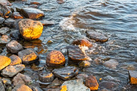 Small waves in a river roll into a rocky riverbank in the early morning light.