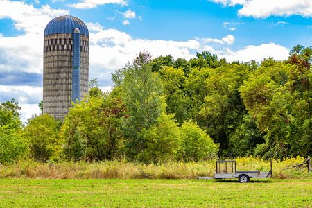 A stave silo for storing grain is seen emerging from surrounding trees, with a trailer sitting in the field below it.