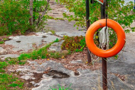 An orange flotation device hangs with rope outside.
