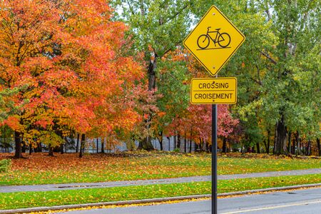 A yellow, bilingual road sign indicates a bicycle crossing with an icon of a bike and a word in both English and French languages. Autumn leaves behind are on trees and fallen on the ground behind it.