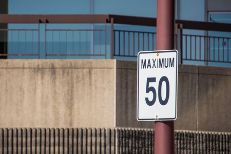 A road sign on a metal post reads Maximum 50 in black lettering on white. No unit of measurement is present, (though in its location it is expected to represent metric kilometers).