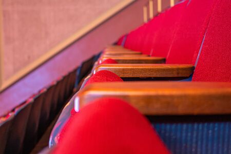 A row of red seats, typical of a theater or a public auditorium, is viewed up close from the side, showing the wooden armrests and red fabric cushioning.