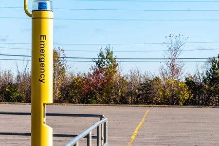 A yellow pole standing in a public parking lot features a blue light and an intercom for requesting help. The word Emergency appears on the side of the lots safety feature.