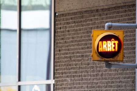 A French-language traffic light on the side of a building illuminates the word Arrêt, meaning Stop. Stock fotó