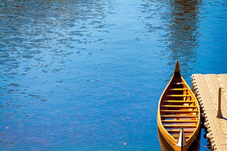 A wooden canoe is tied up with rope at a dock on the side of a river. The vibrant blue and reflective water surrounds it, and a small amount of water can be seen in the boat itself.
