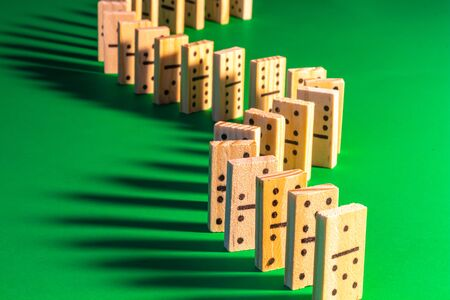A curved line of standing wooden dominoes on solid green is seen lit from the right, producing long shadows falling on the left. The domino show is ready to begin by toppling one of the game pieces.