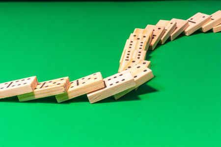 A curved line of dominoes in a domino show has been toppled, with the wooden game pieces cascading across a green surface and lying on top of each other.
