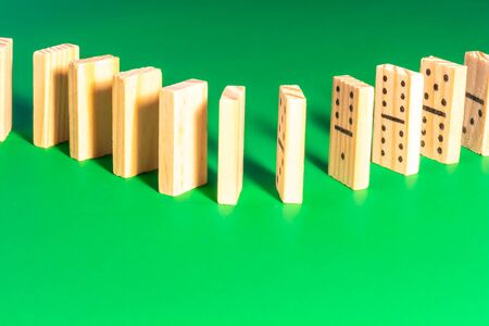 A curve in a line of aligned wooden dominoes stands on a solid green surface. The dominoes are configured not for playing the game, but for knocking over in a domino show.