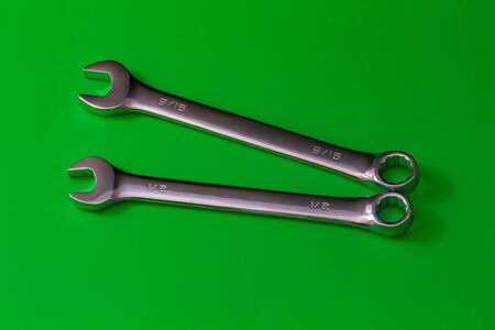 A pair of stainless steel wrenches, combination spanners with both an open end and a box end, lie on a solid green background. their sizes are engraved as fractions of an inch at 12 and 915. Stock fotó