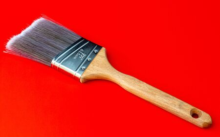 A large format paint brush sits on a solid red background. The paint brush has a wooden handle and polyesternylon bristles emerging from a shiny stainless steel ferrule. Stock fotó