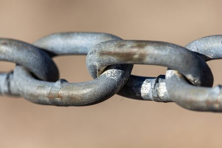 The links of a steel chain are seen up close. The chain is held up taut and viewed against a blurry beige background. Some wear and weathered detail is seen, showing its outdoor exposure.