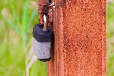 A rusty post along a footpath has a padlock on it, restricting access to an electrical line inside.