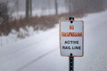 """On a snowy day in winter, a sign placed at the intersection of railroad tracks and a footpath reads, """"No Tresspassing: Active Rail Line"""", warning pedestrians not to wander onto the tracks. Standard-Bild"""