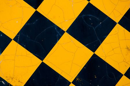 A metal sign marking the end of a road has a black-and-yellow pattern of diamonds. Cracks in its painted surface can be seen. Standard-Bild