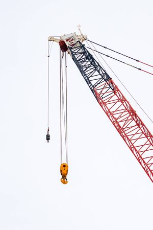 A construction crane has hanging metal pulleys and hooks and does not currently carry anything.