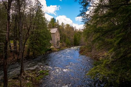 A river rushes past an old stone building in the spring, with whitewater rapids between evergreen and deciduous trees as it runs through the woods. Stock Photo